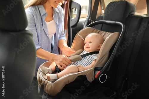 Mother fastening baby to child safety seat inside of car Fotobehang