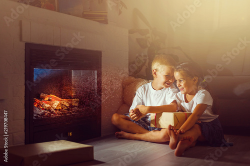 Fotomural happy children with magic gift at home near fireplace