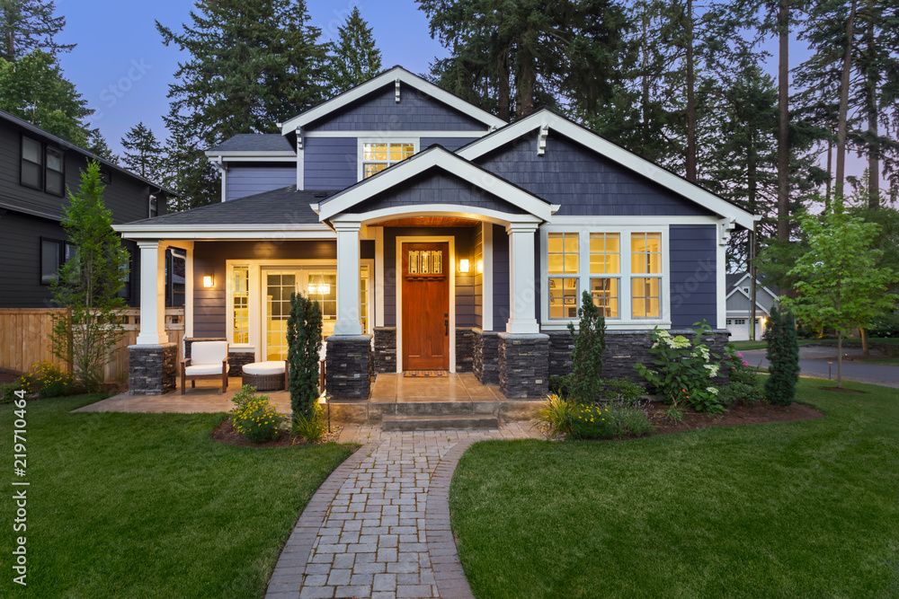 Fototapety, obrazy: Beautiful home exterior in evening with glowing interior lights and landscaping