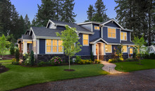Beautiful Home Exterior At Twilight: New House With Beautiful Yard And Landscaping With Gloowing Interior Lights