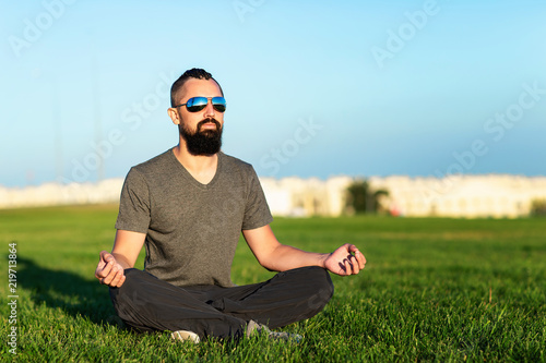 Portrait of bearded meditating man sitting at green grass in lotus pose at city sunset background.