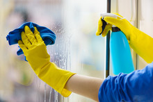 Gloved Hand Cleaning Window Ra...