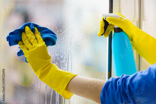 Gloved hand cleaning window rag and spray Canvas