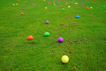 An Easter Egg Hunt With Colorful Plastic Eggs On A Green Lawn