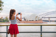 Sydney travel tourist woman taking phone picture of Opera house on Australia vacation. Asian girl using cellphone for photos during holiday.