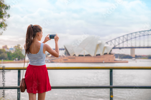 Fototapeta Sydney travel tourist woman taking phone picture of Opera house on Australia vacation. Asian girl using cellphone for photos during holiday. obraz