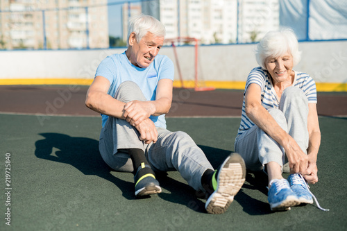 Fotografía  Portrait of white haired senior couple tying sports shoes sitting on running tra