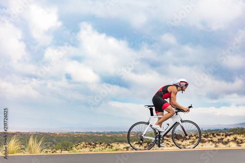 Fényképezés Triathlon cyclist biking on road bike on ironman competition racing against time on nature background landscape