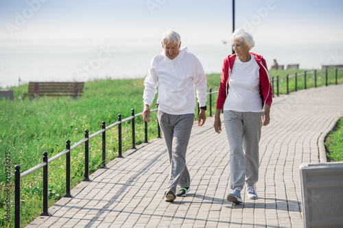 Obraz Full length portrait of active senior couple walking in park and smiling happily while chatting on the way, copy space - fototapety do salonu