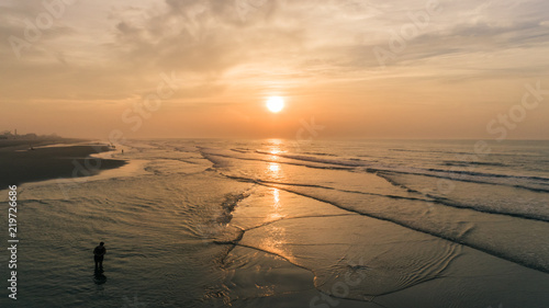 Spoed Foto op Canvas Zee zonsondergang Beach Sunrise over Ocean and waves with cloudy purple yellow orange sky Aerial at New Jersey Shore