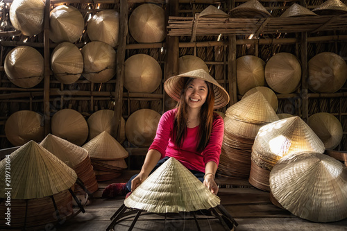 Asian traveler female craftsman making the traditional vietnam hat in the old tr Fototapeta