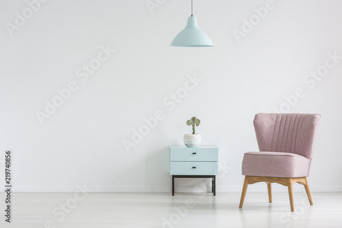Fotografia Pink chair next to cabinet with plant in apartment interior with lamp and copy space