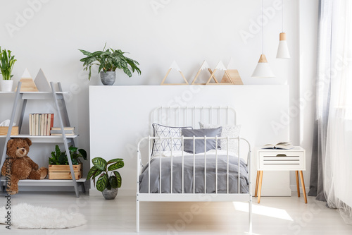 Fotografía  Gray bedding on a single bed with metal frame and a scandinavian style nightstan
