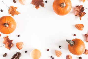 Fototapeta Autumn composition. Pumpkins, candles, dried leaves on white background. Autumn, fall, halloween concept. Flat lay, top view, copy space