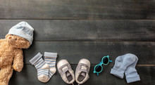 Baby Boy Shoes And Socks On Blue Wooden Background