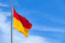 Red And Yellow Flag On A Beach Over Blue Sky