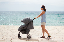 Side View Of Young Mother Pushing Baby Stroller
