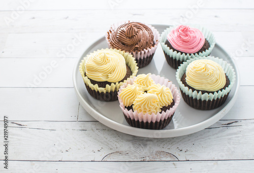 Photo  Frosted pastel cupcakes on white dish and wooden table