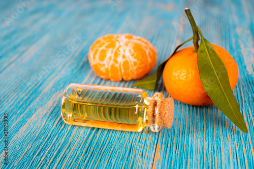 tangerine essential oil with fruits on turquoise wooden table