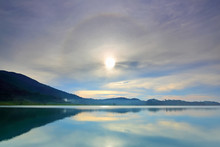 Amazing Sun Halo Above Water With Lake And Mountains