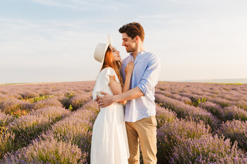 Photo of loving couple young man and woman hugging, while walking outdoor in lavender field