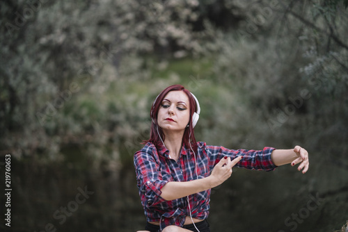 Pretty red haired girl listens to music by the river.