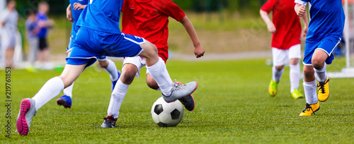 Young Junior Football Match. Players Running and Kicking Football Ball