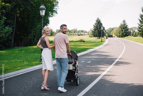 Fototapeta  back view of parents walking with baby carriage on road in park and looking at c