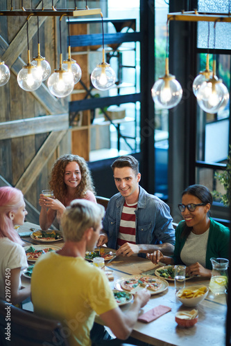 Group of young friendly people in casualwear sitting by served table at dinner and chatting