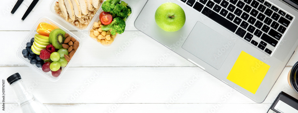 Fototapeta Healthy food in meal box set on working table with laptop