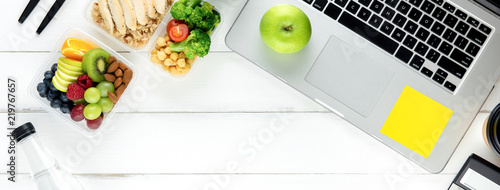 Healthy food in meal box set on working table with laptop