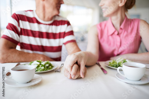 Fototapeta Hands of senior spouses on served table during breakfast between plates with salad and cups of tea obraz