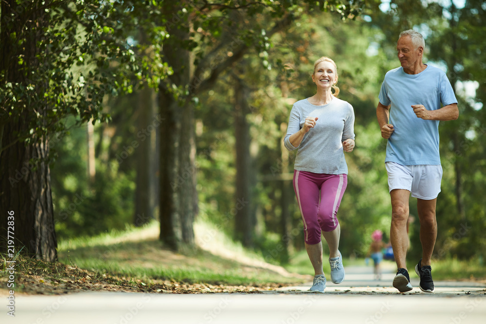 Fototapeta Active and healthy aged couple running in natural environment on summer morning