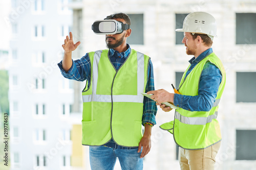 Fotografía  Waist up portrait of two modern construction workers using VR gear to visualize