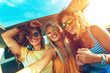 canvas print picture - Three female friends enjoying traveling in the car. Sitting in rear seat and and making selfie.
