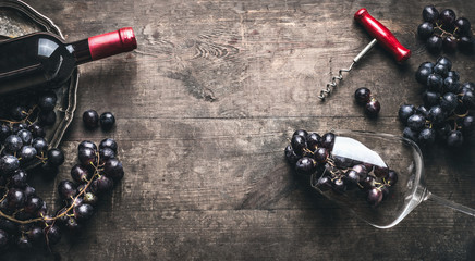 Red wine background with bottle and corkscrew , grapes and wine glass on dark vintage wooden, top view, frame