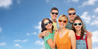 friendship, summer and people concept - group of happy smiling friends in sunglasses hugging over blue sky and clouds background