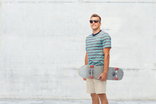 Sport, Leisure And Skateboarding Concept - Smiling Young Man With Skateboard Over Concrete Wall Background