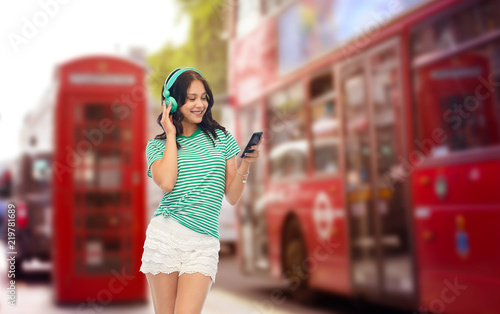 Foto op Canvas Londen rode bus travel, tourism and technology concept - happy teenage girl in headphones with smartphone listening to music over london city street background