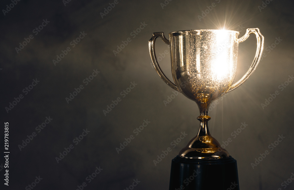 Fototapeta champion golden trophy placed on wooden table