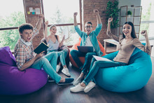 Concept Of Glad, Emotional, Lifestyle And Celebrating Holidays! Units Of The Stylish Guys Sitting At Home Are Happy With The Successful Completion Of Final Exams By Raising Their Fists Up
