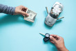 Creative flat lay of woman hand with paper currency and man hand holding key's car