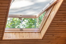 Opened Roof Window With Blinds Or Curtain In Wooden House Attic. Room With Slanted Ceiling Made Of Natural Eco Materials And Park View Through Opened Window. Environment Friendly House