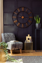 Big Clock On The Black Wall, Armchair, Table And Plant In A Living Room Interior. Real Photo