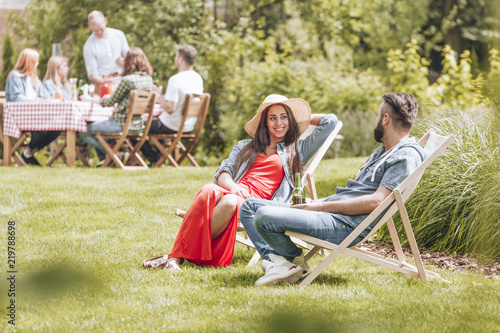Photographie Couple sitting on deckchairs on the grass