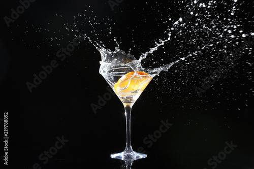 Fotografía  Glass with splashing cocktail and slice of orange on black background