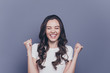 canvas print picture - Attractive pretty charming adorable cheerful stylish brunette curly-haired girl in white t-shirt, showing excitement, closed eyes, isolated over grey background