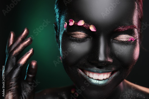 Portrait of beautiful young woman with surreal makeup on dark background, closeup