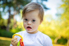 Portrait Of Cute Small Boy With Down Syndrome Playing In Summer Day On Nature With Toys