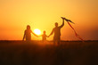 Happy family flying kite in the field at sunset